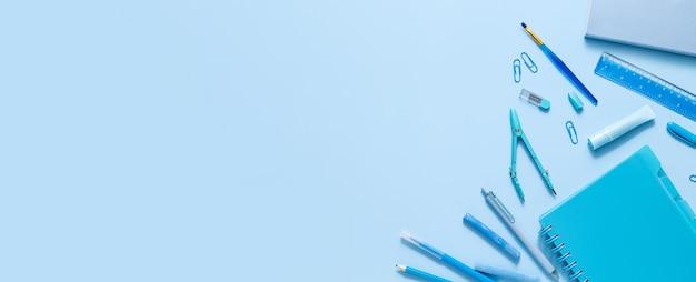 Vista dall'alto di vari articoli di cancelleria su sfondo blu pastello. torna alla bandiera del concetto di scuola con posto per il testo. colore monocromatico