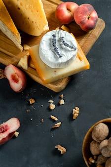 Vista dall'alto su vari tipi di formaggio su sfondo scuro. camembert, formaggio con spezie, formaggio olandese sul tagliere con noci, lavanda e pesca di fichi. copia spazio. cibo piatto. messa a fuoco selettiva e soft
