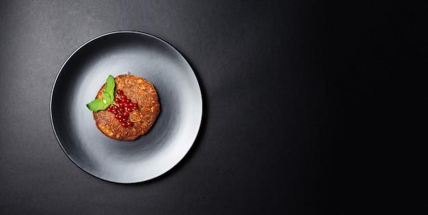 Vista dall'alto del pancake vegano fatto in casa con ribes rosso su banda nera.