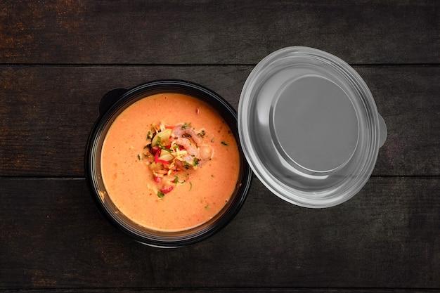 Vista dall'alto della zuppa di crema di verdure con gamberetti in confezione da asporto