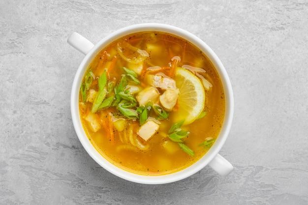 Vista dall'alto di zuppa di verdure e pesce con scalogno fresco