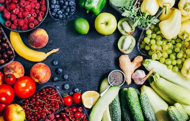 Vista dall'alto di verdure, frutta, bacche su sfondo nero con spazio libero per il testo