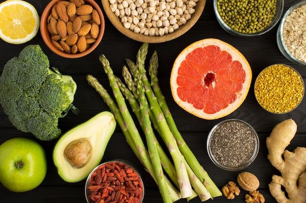 Vista dall'alto di verdure, frutta, legumi, noci e polline d'api