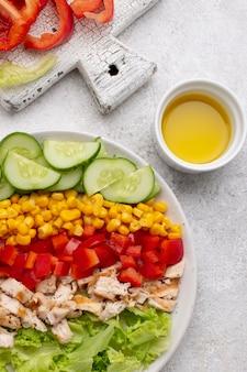 Vista dall'alto insalata vegetariana con pollo e olio