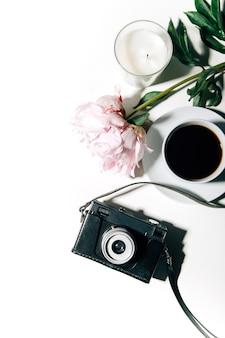 Vista dall'alto della macchina fotografica vintage tazza di caffè candela laptop e fiori su sfondo bianco