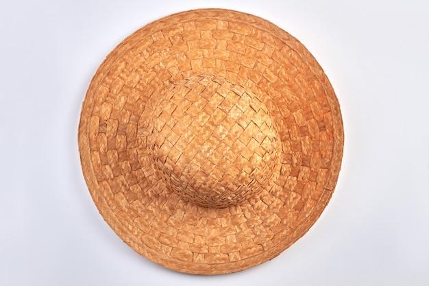 Vista dall'alto del cappello di paglia vintage su bianco. tappo tessuto da vicino. copricapo di protezione solare.