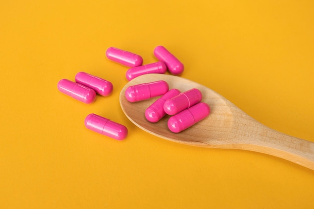 Vista dall'alto di vitamine e minerali pillole sul cucchiaio di legno sullo spazio giallo, prodotto per la cura della salute
