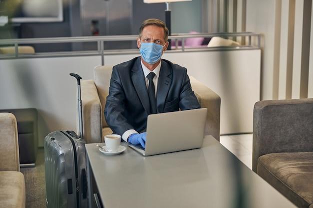 Vista dall'alto ritratto in vita di un uomo elegante in tuta che indossa maschera protettiva e guanti mentre si lavora sul notebook prima del volo