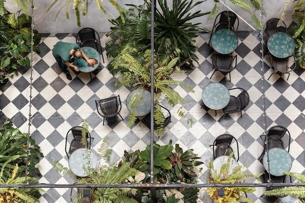 Vista dall'alto del tavolo di pulizia del cameriere in un accogliente caffè all'aperto con pianta.