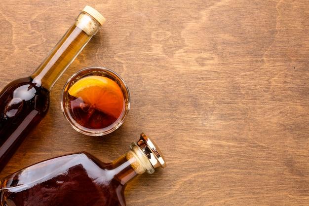 Vista dall'alto whisky e arancia con bottiglie e copia-spazio