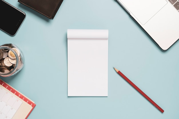 Vista dall'alto di carta bianca bianca con laptop matita rossa e soldi sul tavolo sfondo blu.