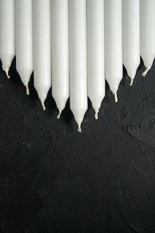 Vista dall'alto di candele bianche sul muro scuro
