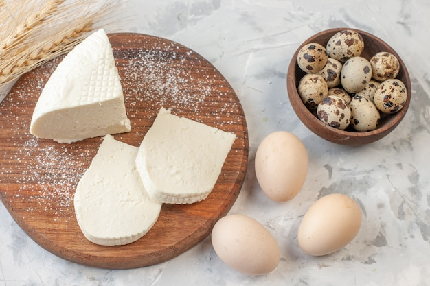 Vista dall'alto fette di formaggio bianco su tavola di legno uova di gallina uova di quaglia in una ciotola di legno spighe di grano sul tavolo