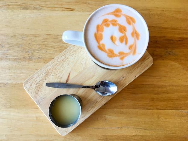 Vista superiore della tazza bianca di tè arancione tailandese con la superficie della schiuma di latte di arte del latte sopra il piatto di legno sulla tavola di legno per la colazione o la pausa caffè.