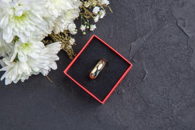 Vista dall'alto fiori bianchi anello in scatola su sfondo scuro con copia posto