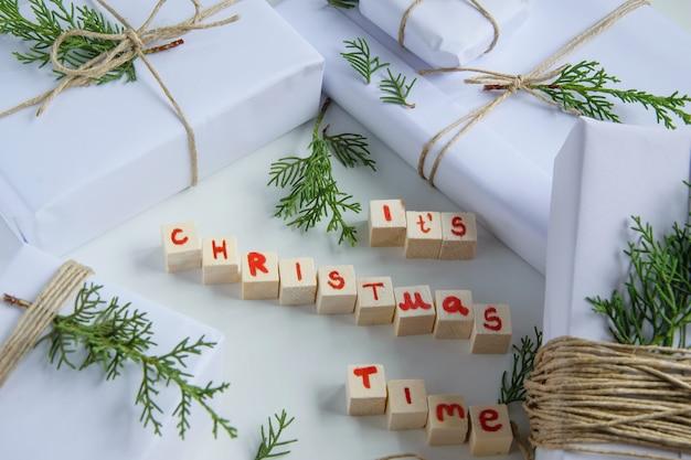 Vista dall'alto di scatole regalo artigianali bianche con lettere in legno di testo natalizio e crusca di abete fresco