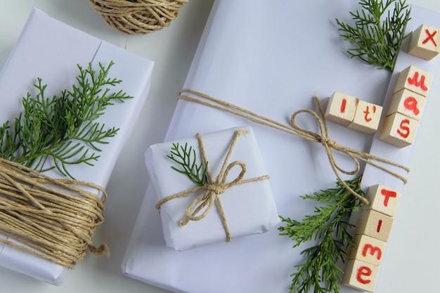 Vista dall'alto di scatole regalo artigianali bianche con le sue lettere in legno di testo x mas e rami di abete fresco