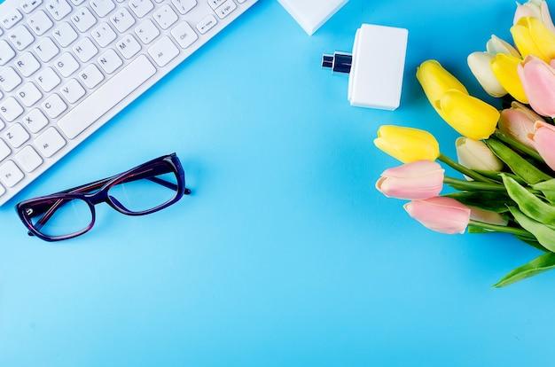 Vista dall'alto della tastiera bianca, occhiali da vista, auricolari, cosmetici e fiori sull'azzurro.