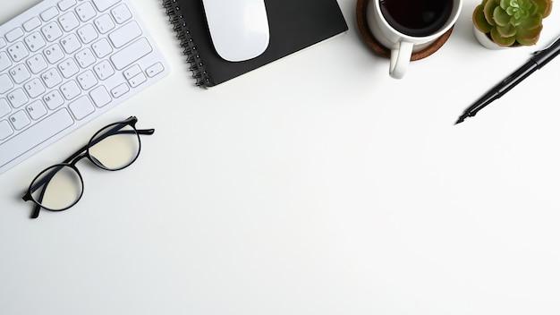 Vista dall'alto della scrivania bianca con tazza di caffè, bicchieri, tastiera, taccuino e copia spazio.