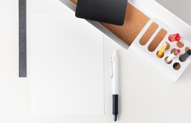Nota di carta bianca vista dall'alto sulla moderna cancelleria per ufficio sul tavolo bianco