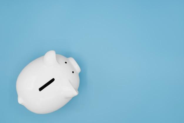 Vista dall'alto del salvadanaio bianco per risparmiare denaro isolato su sfondo azzurro