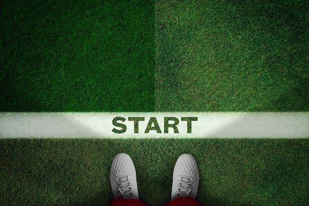 Vista dall'alto di scarpe da calcio bianche sul campo verde con testo inizio