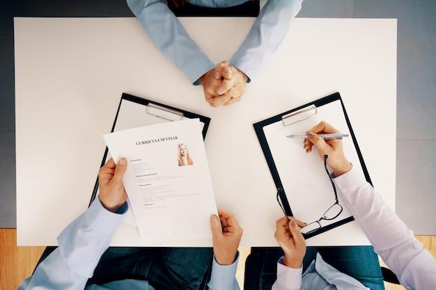 Vista dall'alto del tavolo bianco e delle persone con taccuino legale e cv durante il colloquio di reclutamento