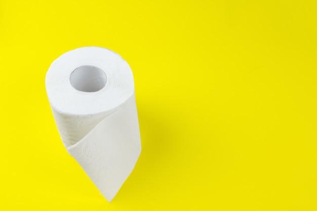Vista dall'alto di rotoli di carta igienica bianca su sfondo giallo con spazio di copia.
