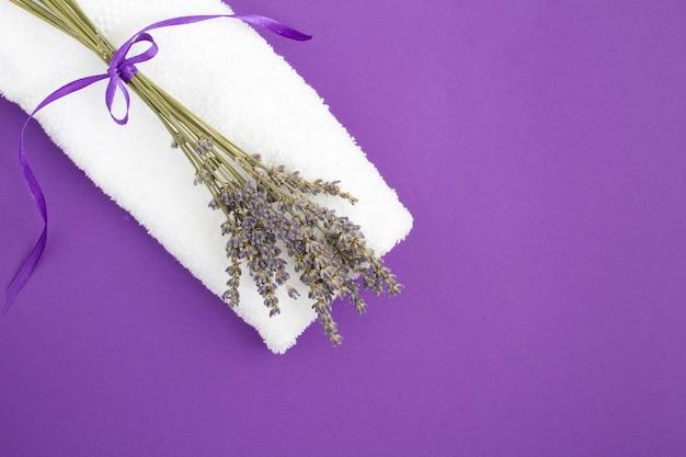 Vista dall'alto di un asciugamano bianco e bouquet di lavanda secca su sfondo viola