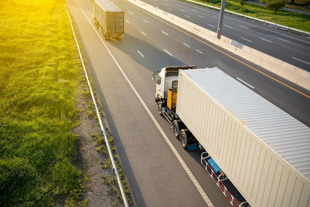 Vista dall'alto al camion bianco sulla strada autostradale con container, concetto di trasporto., importazione, esportazione logistica industriale trasporto trasporto terrestre sulla superstrada. movimento sfocato a soft focus
