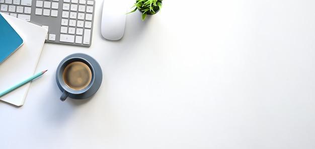 Vista superiore del tavolo di lavoro bianco con i mobili d'ufficio che lo mettono. tastiera del computer, tazza di caffè, pianta in vaso, taccuino e matita piatti. concetto di scrivania moderna e confortevole.