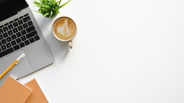 Vista superiore del tavolo di lavoro bianco con i mobili d'ufficio che lo mettono. computer portatile, tazza di caffè, pianta in vaso, taccuino e matita. concetto di scrivania moderna e confortevole.