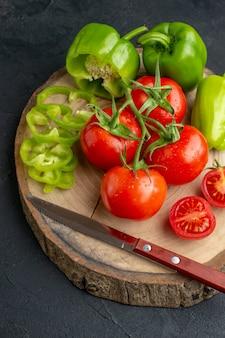 Vista dall'alto di peperoni verdi tritati interi e pomodori freschi sul coltello del tagliere di legno nero sull'asciugamano sulla superficie in difficoltà nera