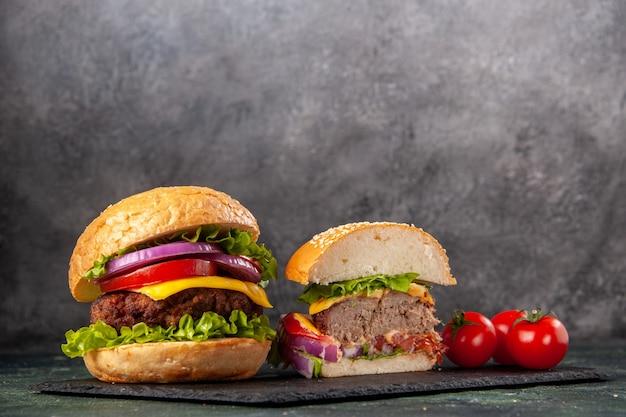 Vista dall'alto dell'intero taglio vari gustosi panini e pomodori con gambo sul vassoio nero su grigio superficie sfocata
