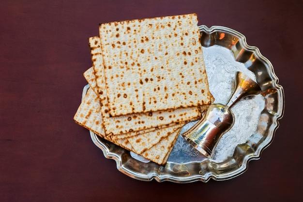Vista dall'alto vino e pane azzimo di pasqua ebraica su sfondo di legno.