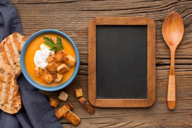 Vista dall'alto della zuppa di zucca invernale con lavagna e crostini di pane