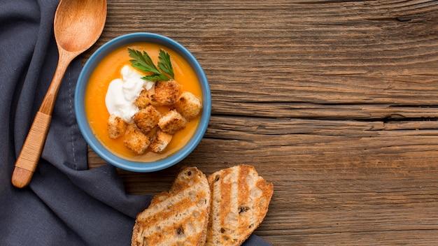 Vista dall'alto della zuppa di zucca invernale con crostini di pane e copia spazio