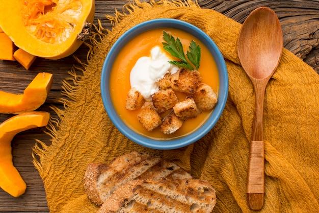 Vista dall'alto della zuppa di zucca invernale con crostini di pane e cucchiaio