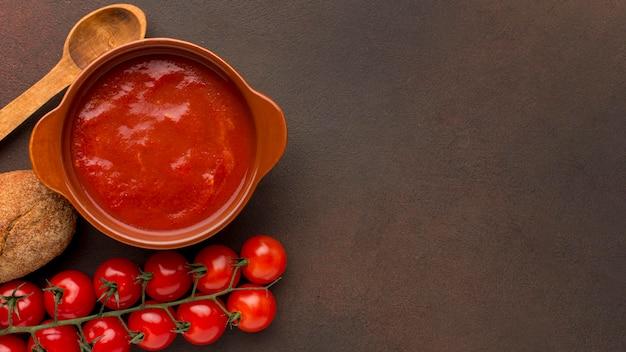 Vista dall'alto della zuppa di pomodoro invernale nella ciotola con il cucchiaio e lo spazio della copia