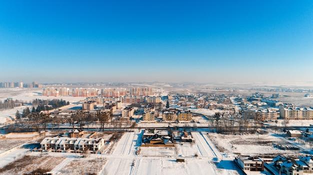 Vista dall'alto del villaggio invernale con case e strade innevate. vista aerea del paesaggio