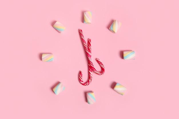Vista dall'alto con marshmallow dolci colorati e lecca-lecca di natale a strisce, bastoncini di zucchero impilati a forma di orologio e quadrante, isolati su sfondo rosa pastello con spazio per la copia per l'annuncio