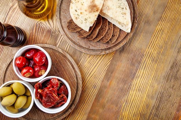 Vista dall'alto con delizioso antipasto italiano. pomodori secchi, olive e peperoni ripieni in spezie italiane in una composizione con pane diverso su fondo in legno. copia spazio. cibo piatto