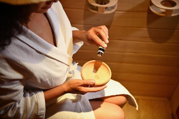 Vista dall'alto di una donna in accappatoio al vapore nella sauna e che versa alcune gocce di olio essenziale in un mortaio di legno. avvicinamento. concentrati sulle mani
