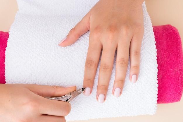 Donna di vista superiore che fa la sua manicure