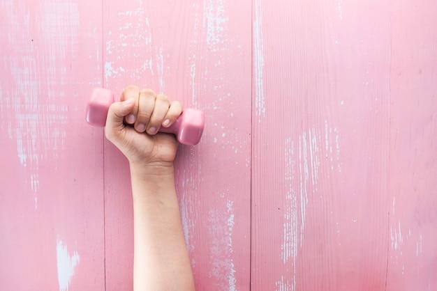Vista superiore della mano della donna che tiene testa di legno rosa.