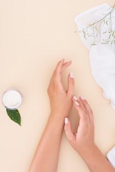 Mani di donna vista dall'alto su sfondo beige