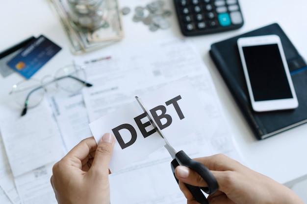 Vista superiore del taglio delle mani della donna della carta con il debito di parola scritto su.