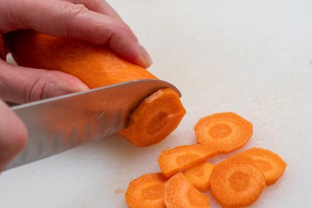 Vista dall'alto delle mani della donna che tagliano le carote crude in fette rotonde usando un coltello su uno sfondo bianco.