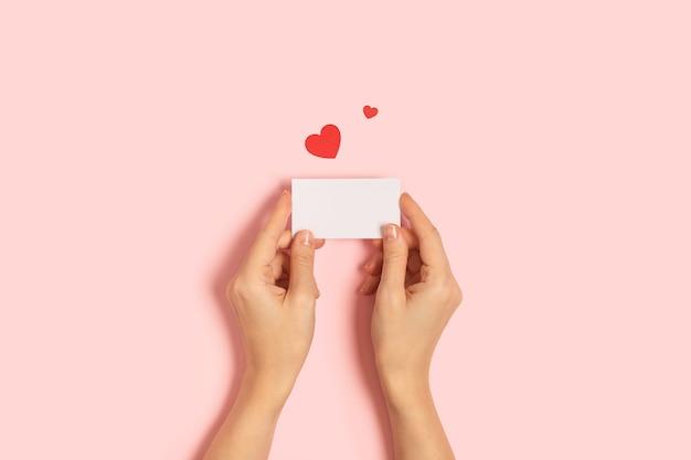 Vista dall'alto delle mani di donna che tengono carta bianca saluto o carta di invito su sfondo rosa pastello con coriandoli