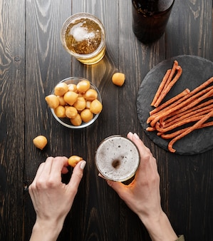Vista dall'alto delle mani di una donna che tengono un bicchiere di birra e uno spuntino al formaggio in legno nero sullo sfondo